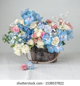 Close-up composition with a with different flowers.Delphiniums and roses .Many beautiful fresh flowers on a table. Pastel colors.