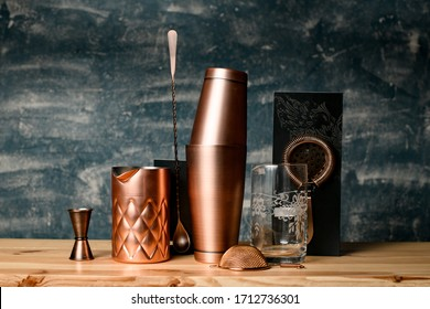 Close-up composition of several copper items of bar equipment which stands on wood surface at bar.