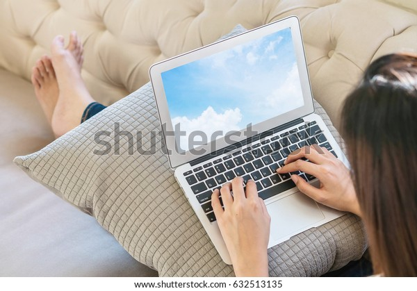 Closeup computer notebook on woman lap with sitting on sofa for work action in lifestyle of woman concept