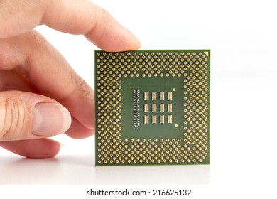 Close-up of a computer processor microchip between the fingers and isolated on a white background