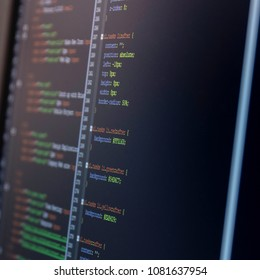 Close-up of a computer screen with HTML and CSS code, black background