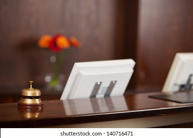 Closeup of computers and bell at reception counter in hotel