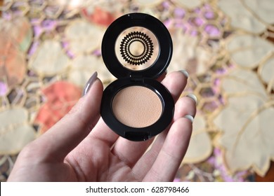 Close-up of concealer in female hand against autumn leaves pattern background, make-up and beauty care concept