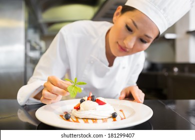 Closeup of a concentrated female chef garnishing food in the kitchen