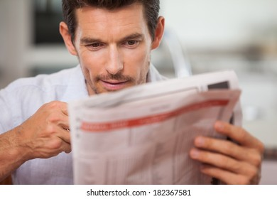Close-up of a concentrated young man reading newspaper at home