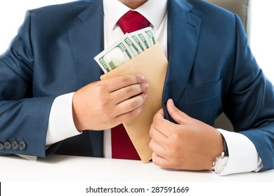 Closeup conceptual photo of bribed man putting money in the suit pocket