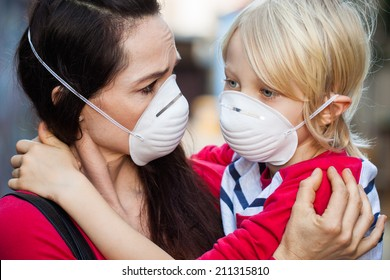 Close-up of a  concerned woman looking at her sick son. Both are wearing protective face masks for pollution or virus.