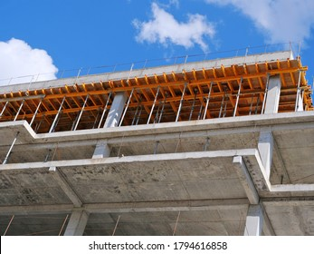 Closeup of concrete frame structure showing formwork for concrete slab sustained by steel (staging). New multi-story apartment building in construction.