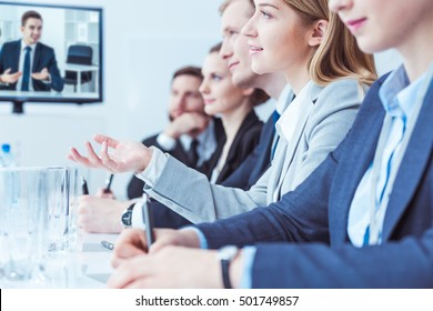 Close-up of conference participants sitting in a row at a conference table, a young woman asking questions