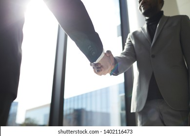 Close-up of confident business partners in suits standing at panoramic window and making handshake after concluding deal