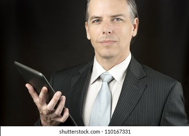 Close-up of a confident businessman holding  tablet.