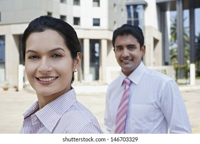 Closeup of confident businesswoman and businessman standing outside building