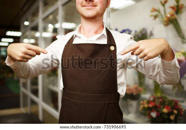 Close-up of a confident florist in a brown apron on a shop background. Florist uniform concept.