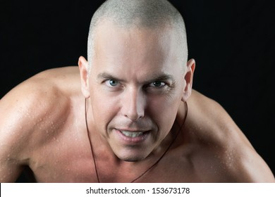Close-up of a confident man looking to camera, shirtless, shaved head