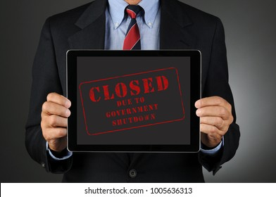Closeup of a Congressman holding a tablet computer in front of his torso with the Closed Due to Government Shutdown.