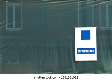 The close-up of a construction site tarp with a sign for rent.