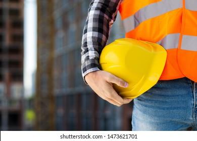 Close-up construction worker holding helmet