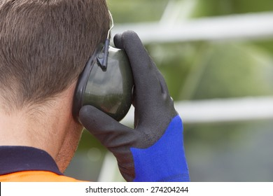 Closeup of construction worker wearing ear protectors at storage tank park
