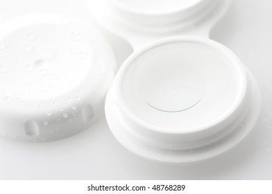 Close-up of contact lenses in container with solution. Selective focus on front edge of lens.
