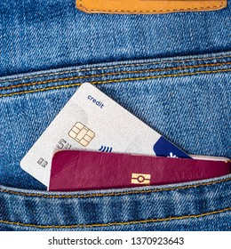Closeup of a contactless credit card and EU passport peeking out of blue jeans back pocket. Travel or shopping, emigration concept.
