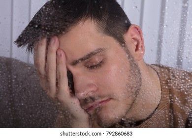 Close-up Of A Contemplating Young Man Behind Window