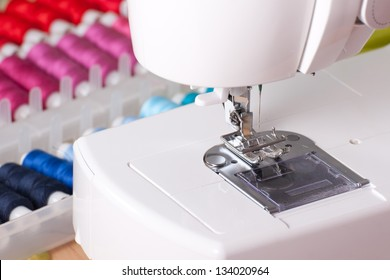 Close-up of contemporary sewing machine with colored spool box.