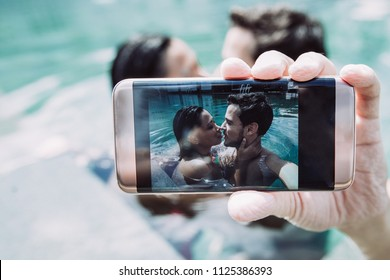 Closeup of content young interracial couple taking selfie photo at edge of swimming pool with focus on smartphone screen. Front view.
