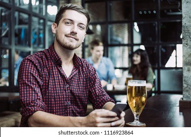 Closeup of content young man looking at camera, using smartphone and sitting at table with glass of beer in pub with other customers in background