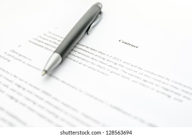 Closeup of a contract and a pen. Focus on a contract sign.