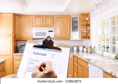 Closeup of a contractors clipboard as he writes up an estimate for a kitchen remodel. Shallow depth of field with focus on clipboard.