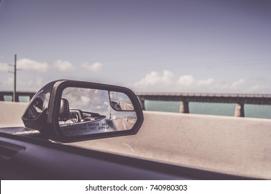 Closeup of convertible side mirror reflection riding on overseas highway to Key West Florida