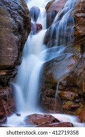 Closeup of cool colored waterfalls against red colored rocks. Hays Creek Falls near Redstone, Colorado