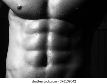 Closeup of cool perfect sexy strong sensual bare torso with abs pectorals and 6 pack muscles and muscular chest black and white studio, horizontal picture