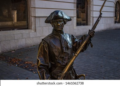 Close-up of copper statue representing a soldier standing guard with a musket with building in the background