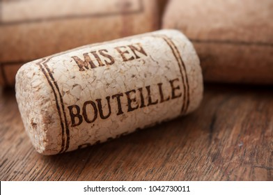 closeup of cork wine stopper with text - bottled on wooden table background  (traduction text in french - mis en bouteille)