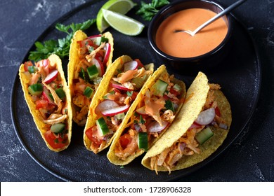 close-up of Corn Taco shells loaded with shredded chicken breast, fresh greens and vegetables on a black plate with lime and buffalo sauce on a concrete table, horizontal view from above