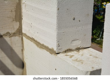 A close-up of a corner of a masonry wall made from autoclaved aerated concrete blocks (AAC) with a sawn concrete brick for a window area.
