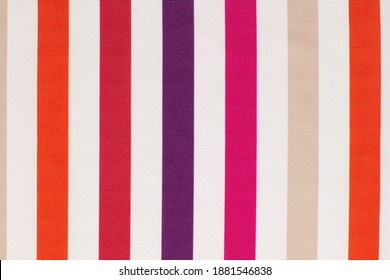Closeup cotton fabric texture with red, orange, pink and purple stripes. Abstract background with copy space.