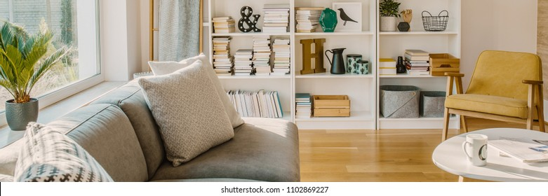 Close-up of a couch with pillows standing by the window, white bookshelf and armchair in a living room interior
