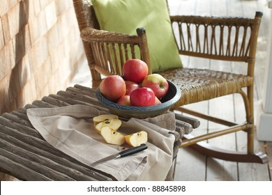Closeup of country porch outdoors with apple still life on rustic table and antique rocking chair. Cedar shingles in background. Horizontal format and copy space.