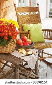 Closeup of country porch outdoors with apple still life on rustic table and antique rocking chair. Cedar shingles in background and a vertical format.