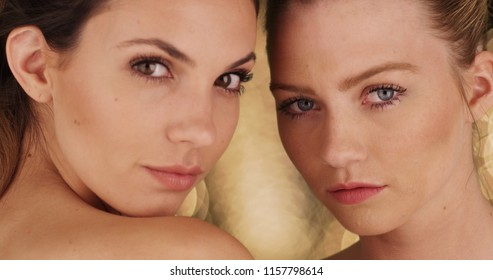 Close-up of couple beautiful models looking at camera on bright background