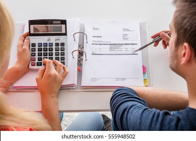 Close-up Of Couple Calculating Family Budget, Invoices, Insurance And Tax Using Calculator At Home