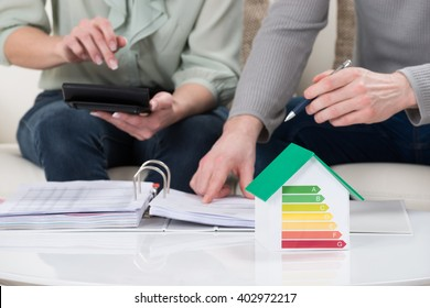 Close-up Of Couple Calculating Tax With House Model Showing Energy Efficiency Rate On Desk