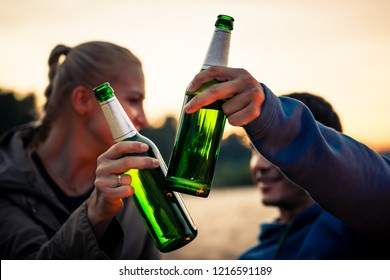 Close-up of couple clinking their beer bottles outdoors