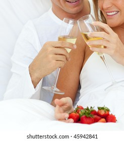 Close-up of a couple drinking Champagne with strawberries lying on their bed
