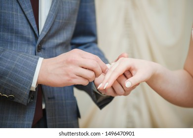 Closeup of couple exchanging wedding rings during their wedding ceremony. Cropped shot of groom putting a wedding ring on the finger of the bride.
