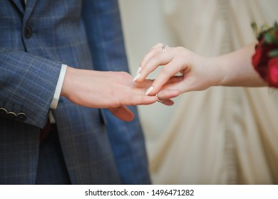 Closeup of couple exchanging wedding rings during their wedding ceremony. Cropped shot of bride putting a wedding ring on the finger of the groom.