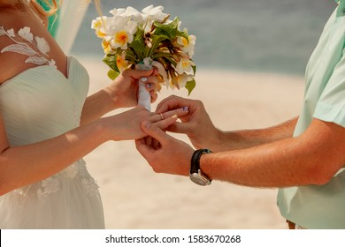 Closeup of a couple exchanging wedding rings during a wedding ceremony on the beach. Wedding and honeymoon concept.