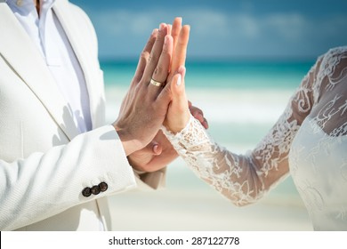 Closeup of a couple exchanging wedding rings during a wedding ceremony on the beach. Destination wedding.
